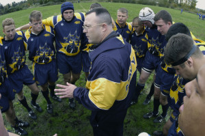 031022-N-6477M-384  Smokey Point, Wash. (Oct 22, 2003) -- U.S. Navy rugby team head coach, Cmdr. Don Sheehan, assigned to Naval Air Station (NAS) Patuxent River, Md. instructs the team before their first match against the U.S. Air force at the Naval Support Center in Washington.  U.S. Navy photo by PhotographerÕs Mate 2nd Class Eli Jody Medellin.  (RELEASED)